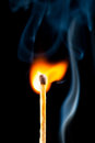 Igniting match with smoke black background Stock Images