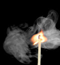 Ignition of a match with smoke on dark background Royalty Free Stock Photo