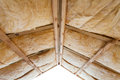 Iinsulation of attic with fiberglass cold barrier and insulation material.