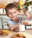 Il bambino felice versa il latte dalla brocca Fotografie Stock