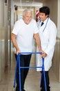 Il dottore assisting old man su un camminatore Fotografie Stock