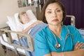 Il dottore Standing With Arms Crossed nella stanza dei pazienti Fotografie Stock