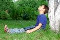 Il taccuino del ragazzo si siede l'albero Fotografie Stock