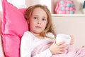 Ill child at home with hot tea in the bed Stock Images