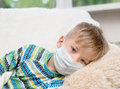 Ill little boy in medicine health-care mask lying on bed