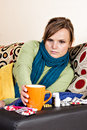Ill woman holding a cup of tea sitting at home on couch Royalty Free Stock Photo