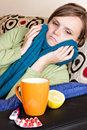 Ill woman resting on couch at home Stock Images