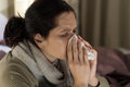 Ill woman sneezing in a tissue young sick sweating from flu fever Stock Photos