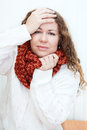 Illness woman with headache holding hands behind her head in wool scarf Royalty Free Stock Image