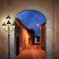 Illuminated alleyway with arched gate and lantern moody burning Royalty Free Stock Images