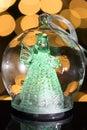 Illuminated angel figure in glass bulb, soft boke christmas ligh Royalty Free Stock Photo