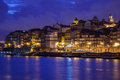 Illuminated city buildings and boats reflecting colorful lights into Douro River along waterfront in Porto, Portugal Royalty Free Stock Images