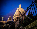 The illuminated domes of Sacre Coeur, Paris, against a deep blue night sky Royalty Free Stock Photo