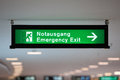 Illuminated green emergency exit sign hanging from the ceiling in a public transportation facility shows a figure exiting Stock Photo