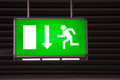 Illuminated green exit sign attached to the ceiling in a public transportation facility signage consists of a human figure running Royalty Free Stock Image