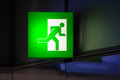 Illuminated green exit sign attached to a wall in a public transportation facility signage consists of a human figure running and Stock Photo