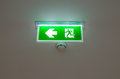 Illuminated green exit sign suspended from the ceiling Royalty Free Stock Photo