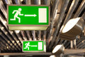 Illuminated green exit signs mounted to ceiling Royalty Free Stock Photo