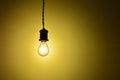 Illuminated hanging led  light bulb over orange background Royalty Free Stock Photo