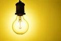 Illuminated hanging light bulb close up of an over orange background Royalty Free Stock Images
