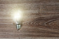 Illuminated light bulb on wood common laying wooden board Stock Image