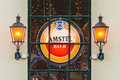 Illuminated sign with the Dutch Amstel Beer logo behind a window Royalty Free Stock Photo