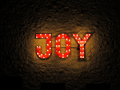 Illuminated sign joy an red with the word fixed outside on a brick wall picture taken by night Stock Photo