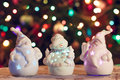 Illuminated Snowman and Jack Frost (Santa Claus) dolls in front of Christmas tree lights, blurred background