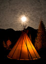 Illuminated teepee under the full moon. Royalty Free Stock Photo