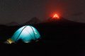 Illuminated tourist tent at night on background erupting volcano Royalty Free Stock Photo