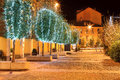 Illuminated trees alba italy row of for christmas holidays on cobbled street at night in northern Royalty Free Stock Photo