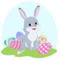 Illustration of the rabbit, colored Easter eggs and blue sky.