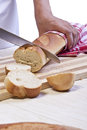Image of a baker s hand holding a knife slicing baguette roll on a wooden board Royalty Free Stock Photos