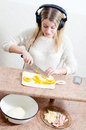 Image of beautiful blond cheerful young woman with headphones listening to music making pizza portrait pretty girl having fun food Stock Photography