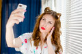 Image of beautiful elegant pinup girl having fun taking selfie photo with mobile smart phone young pretty woman at home by window Stock Image
