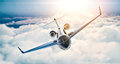 Image of black luxury generic design private jet flying in blue sky at sunset. Huge white clouds background. Business