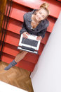 Image of blond young pretty business or female student having fun working typing on laptop computer relaxing sitting on stairs Royalty Free Stock Photo