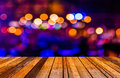 Image of blurred bokeh background with colorful lights blurred wood table and Royalty Free Stock Images