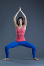 Image of charming young yoga trainer shows asana on gray background Stock Photography