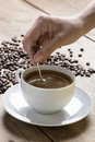 Image of a coffee cup being stirred by a white human hand on a wooden table top surrounded raw beans Stock Images