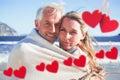 Image composée des couples de sourire enveloppés dans la couverture sur la plage Image stock