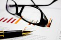 Image containing business charts with glasses and pen illustrating business analysis and financial review Stock Image