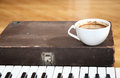 Image of cup of coffee and a piano Royalty Free Stock Photos