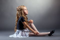 Image of curly blonde dancer sitting in studio on gray background Royalty Free Stock Image
