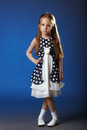 Image of cute girl posing in blue polka dot dress on background Royalty Free Stock Image