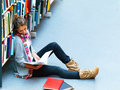 Image of a female student sitting by bookshelf Stock Images