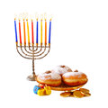 image of jewish holiday Hanukkah with menorah (traditional Candelabra), donuts and wooden dreidels (spinning top).isolated Royalty Free Stock Photo