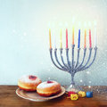 Image of jewish holiday hanukkah with menorah traditional candelabra donuts and wooden dreidels spinning top retro filtered Stock Image