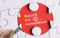 Image of magnifying glass focusing on return on investment Stock Images