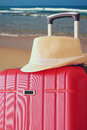 Image of red elegant travel luggage and fedora hat in front of sea. travel and vacation concept Royalty Free Stock Photo
